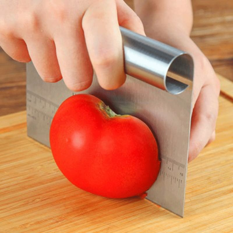 A hand holding an apple in front of a wooden cutting board